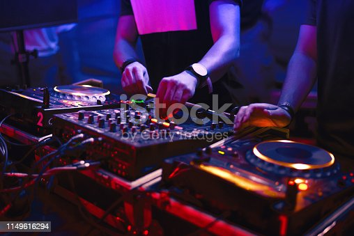 Two dj's mixing music in the nightclub.