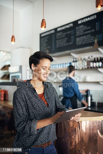 Shot of a young woman using a digital tablet in a coffee shop with her colleague standing in the background
