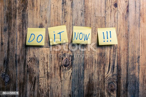 Do it now text on yellow post it notes attached to a wood background