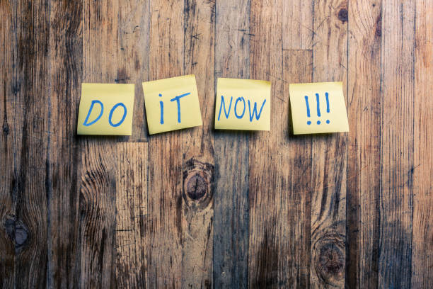 Do it now !!! Do it now text on yellow post it notes attached to a wood background taking the plunge stock pictures, royalty-free photos & images