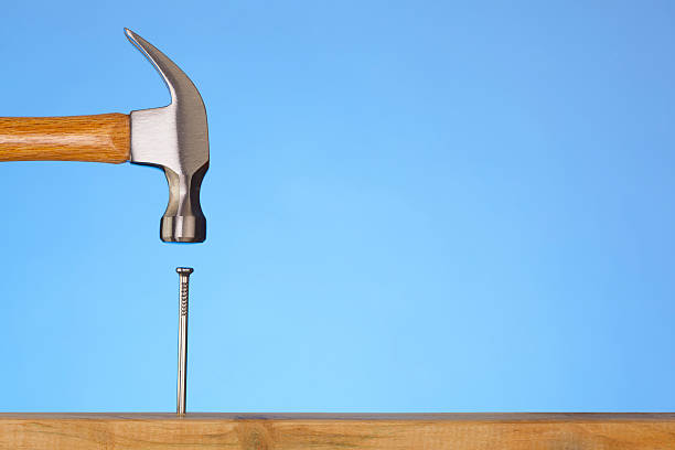 Do It Yourself; Hammer Hitting Nail On The Head stock photo