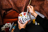 istock DIY. Do it yourself. Woman paints thanksgiving decorations on orange pumpkin for Halloween. Autumn harvest 1328806621
