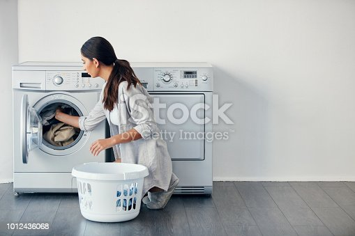 Shot of a young attractive woman doing her laundry at home
