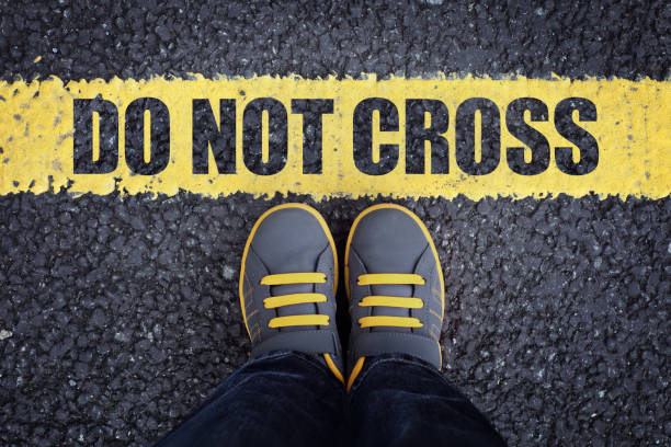 Do not cross the line Do not cross line child in sneakers standing next to a yellow line with restriction or safety warning boundary stock pictures, royalty-free photos & images