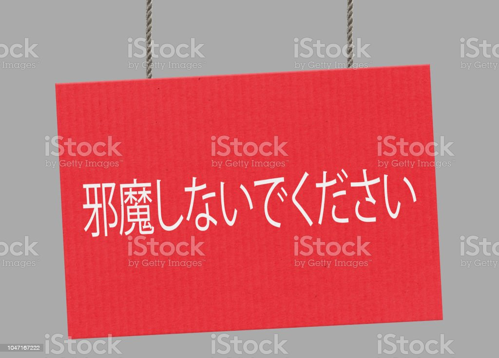 Do not disturb japanese sign hanging from ropes. Clipping path included so you can put your own background. stock photo