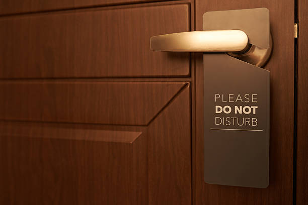 Do not disturb Closed door of hotel room with please do not disturb sign coathanger stock pictures, royalty-free photos & images
