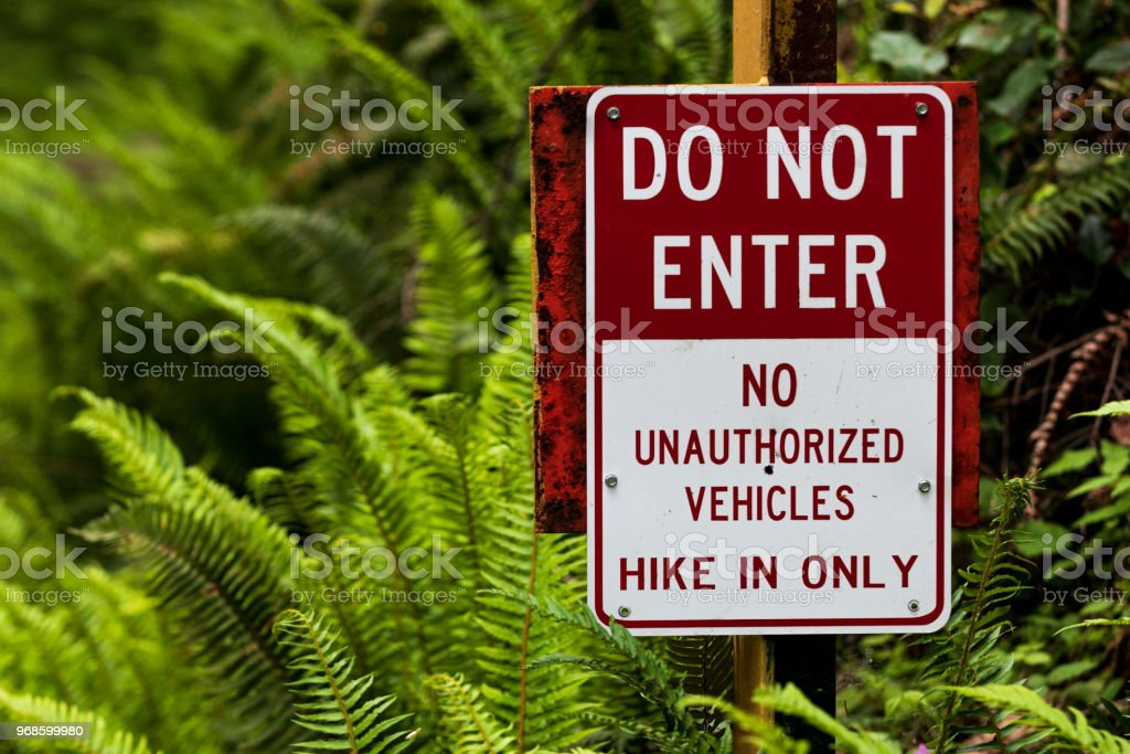 Do not enter hike in only sign no unauthorized vehicles with plants stock photo