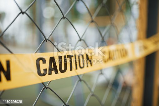 Do not enter. Yellow caution tape on the metal fence at daytime. Crime scene.