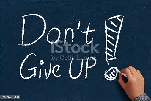 Do not give up on blue chalkboard with the hand of businessman.