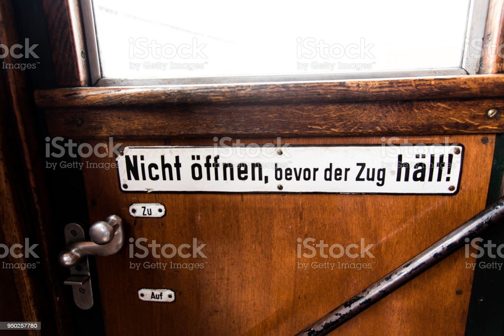 Do not open before train stops - sign in historic train wagon stock photo