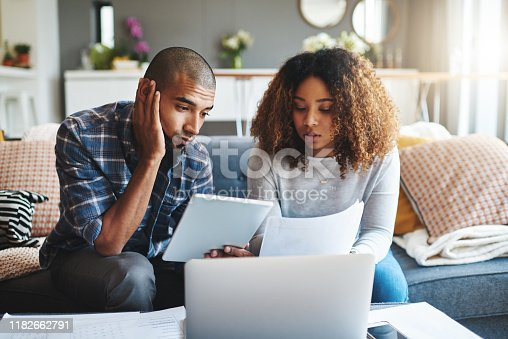 Cropped shot of a stressed young couple sitting together and using a laptop to go over their financial paperwork