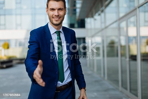 Young businessman in a suit offering a handshake