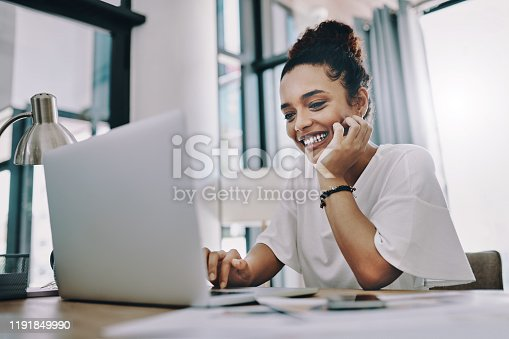 Shot of a young businesswoman using a laptop while working in her home office