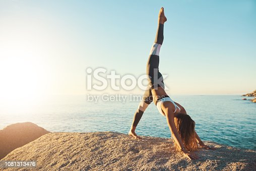 Shot of an athletic young woman practicing yoga on the beach