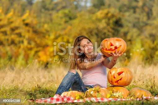 excited and happy woman sitting and holding her Halloween pumpkin, showing in and being proud of her work.