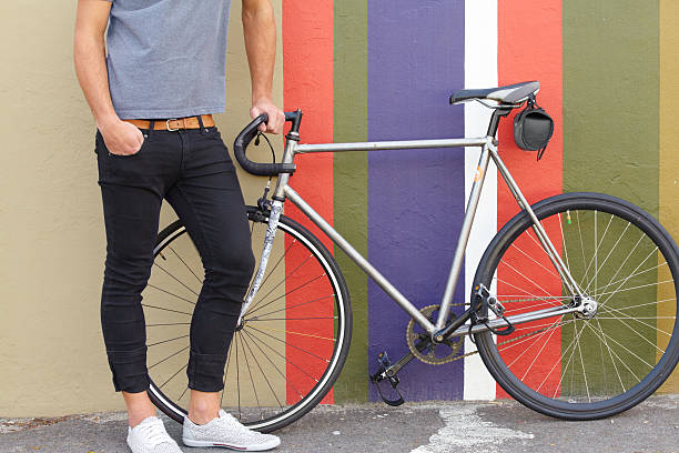 Do you like my ride? Cropped shot of a stylishly dressed young man standing next to a bicycle against a colourful background skinny jeans stock pictures, royalty-free photos & images