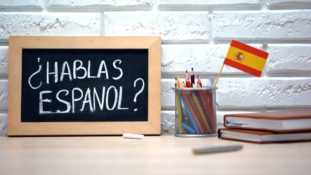 Do you speak Spanish written on board, international flag in box, language stock photo