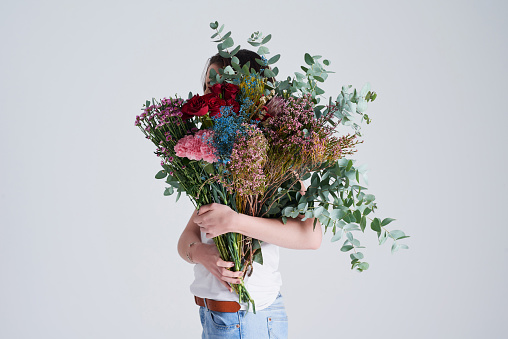 Studio shot of an unrecognizable woman covering her face with flowers against a grey background