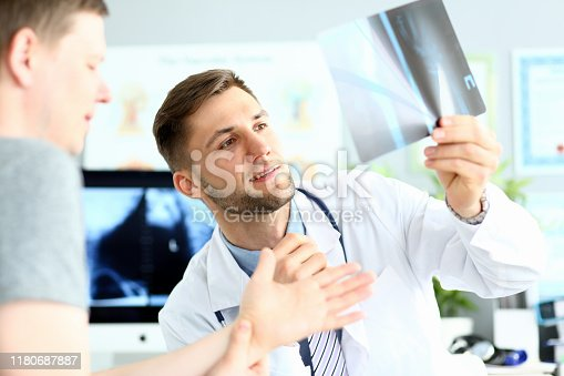 Portrait of doctor examining radiogram picture. Smiling physician pleased with results of treatment. Medicine and health care concept. Blurred background