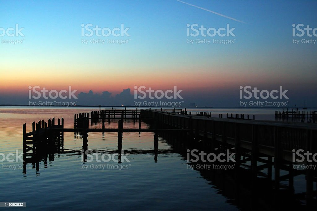 Dock at Sunrise The dock at Space View Park in Titusville, Florida at sunrise with Kennedy Space Center in the background Beach Stock Photo