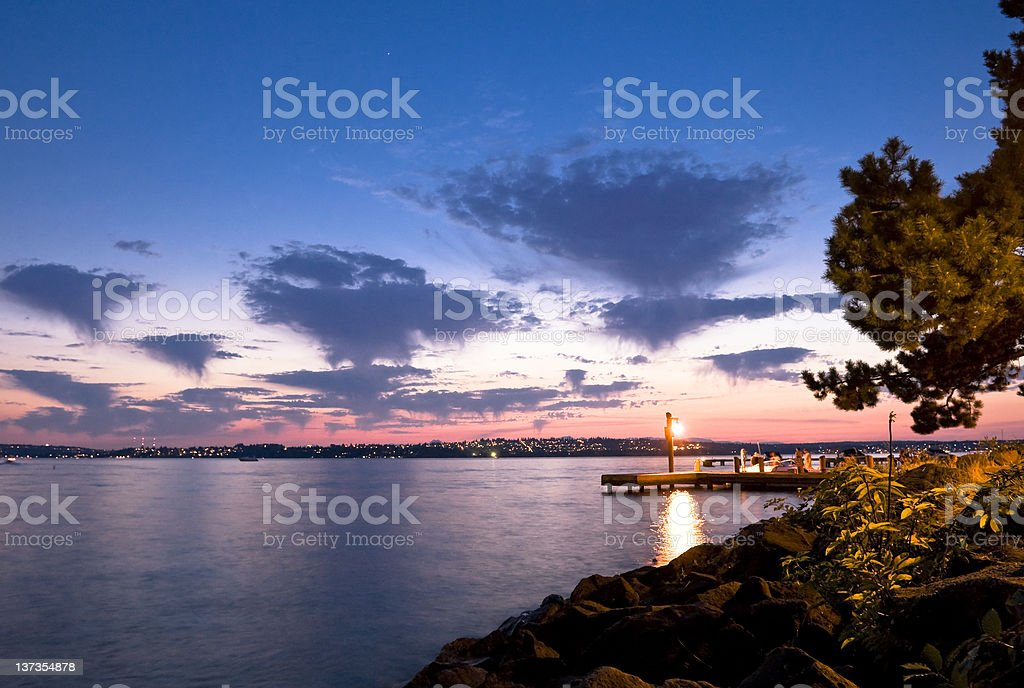 Dock lit up as the sun sets over the lake royalty-free stock photo