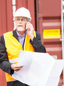 Mature dock worker, maneger, with white helmet and glasses with a mobile and checking consignment notes against pallet of cargo container in background.