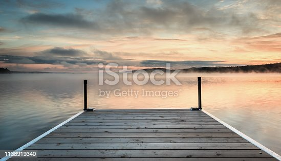 Wooden dock on a orange and blue misty lake at sunrise