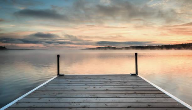 dok op een kalm en mistig meer bij zonsondergang - kade stockfoto's en -beelden