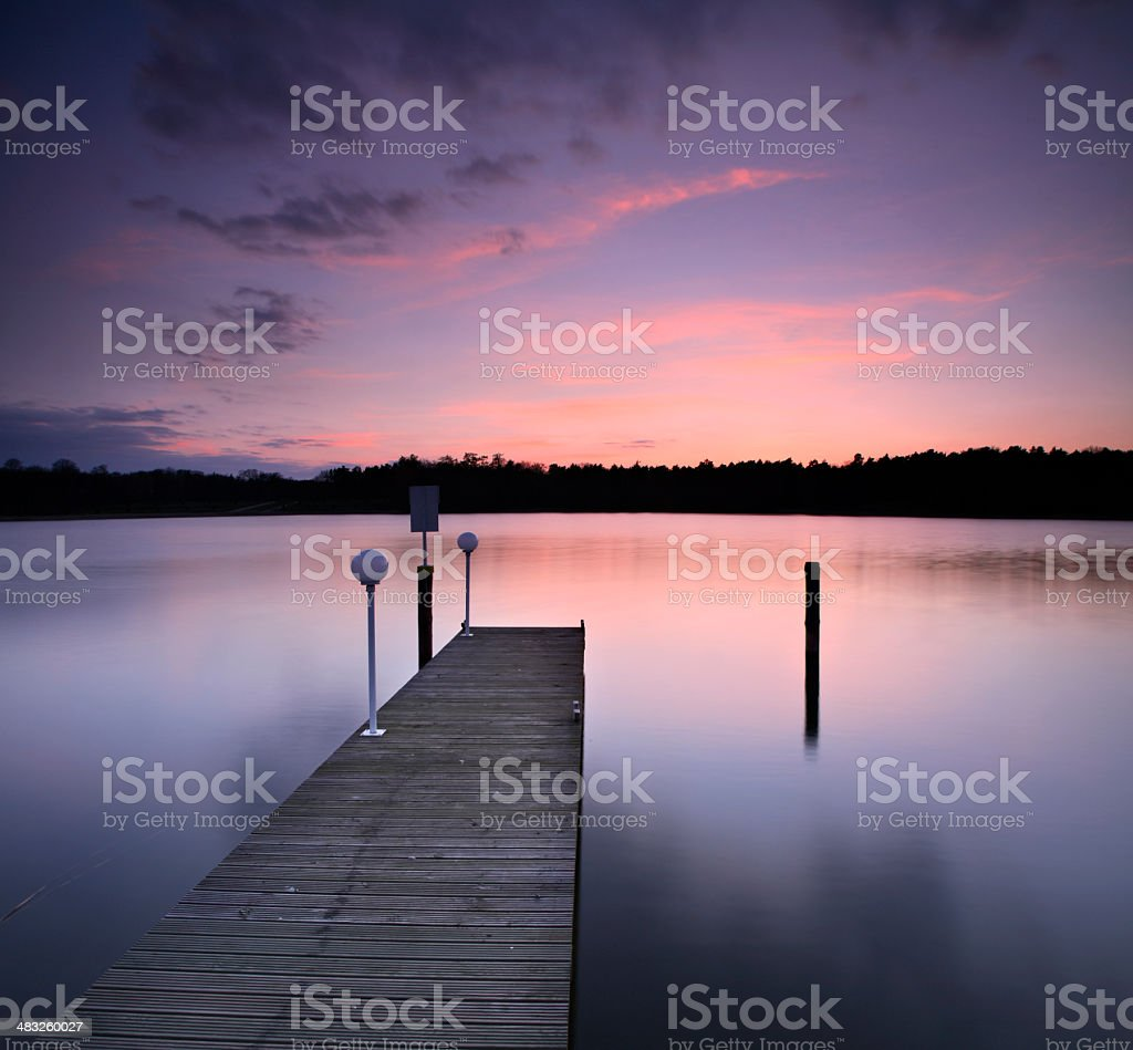 Dock on Calm Lake at Sunset royalty-free stock photo