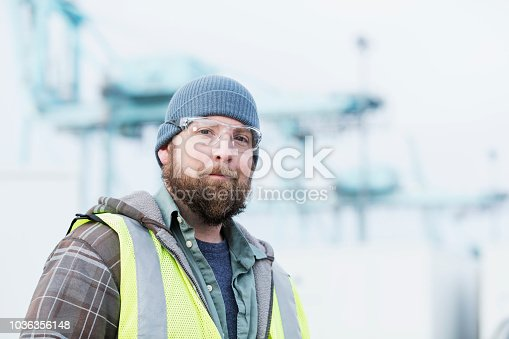 A mid adult man with a beard in his 30s working as a dock worker at a shipping port. He is wearing a knit hat, safety vest, and safety glasses, looking toward the camera. A gantry crane is out of focus in the background.