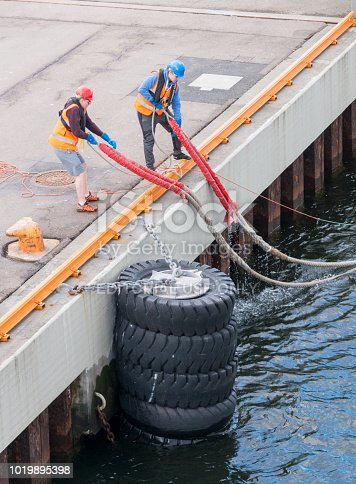 Oslo, Norway - April 26. 2018 - Harbor workers with rope secure a docking ship in the harbor of Oslo. Cruise ships dock here so passengers can visit the city of Oslo for a few days.