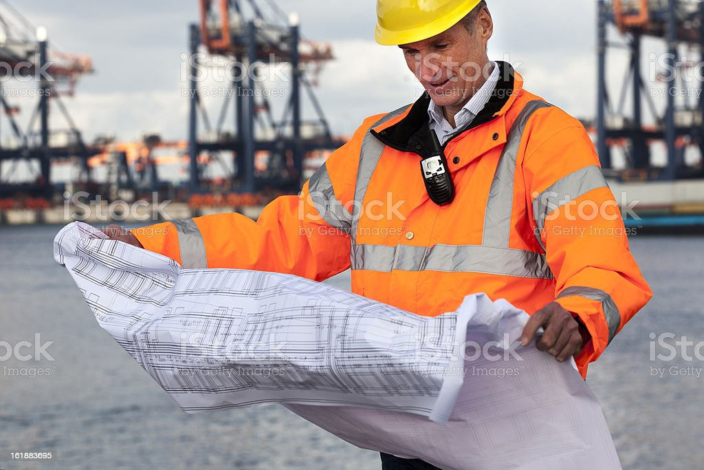 Dock worker reading a plan stock photo