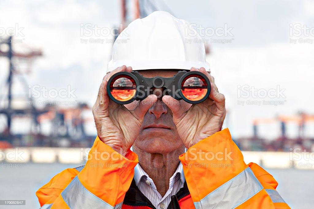 Dock worker with binoculars stock photo