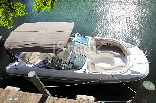 Close up elevated view of docked beautiful boat at wooden dock on canal in Florida, USA