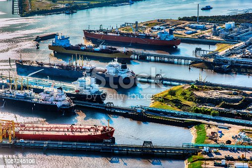 A group of international oil tankers docked at an oil refinery loading fuel for transport to various nations around the world.  This aerial shot is a refinery located just outside of Houston, Texas.