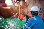 stevedore foreman takes control over walkie talkie to working safety of the shaft of the propeller of the ship replacement in the sea port