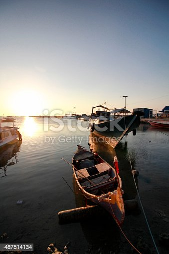 Boat docked by the sunset harbour of Karimunjawa Island Indonesia
