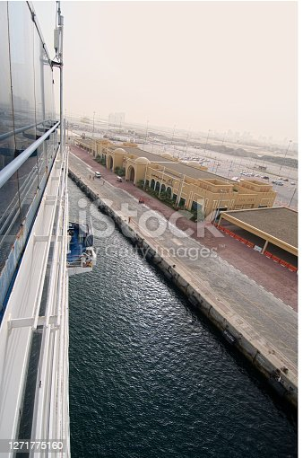 Docking the cruise ship in Dubai with a cloudless hazy desert sky and tiny little people on the ground ready to moor the ship