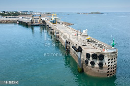 Ship is lining up to dock at the port. The loading ramp for vehicles is clearly visible. It is a calm day in May. A group and a pair of dockers can be seen waiting to help with docking.