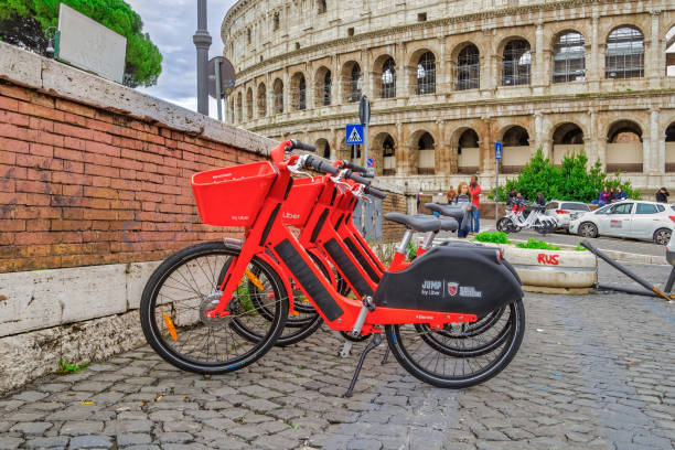 Dockless Electric Bicycle sharing system rentals with basket on a sidewalk at Colosseum area in the Roman capital. stock photo