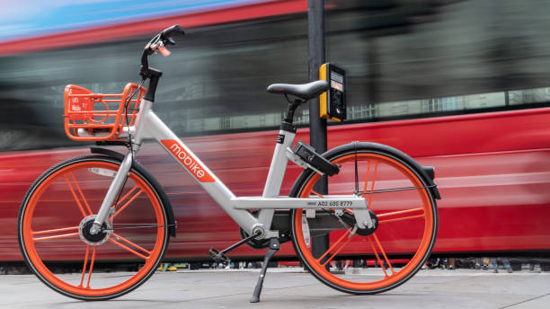 Dockless Elektrofahrrad vor verschwommenen Doppeldecker-Bus in London, UK – Foto