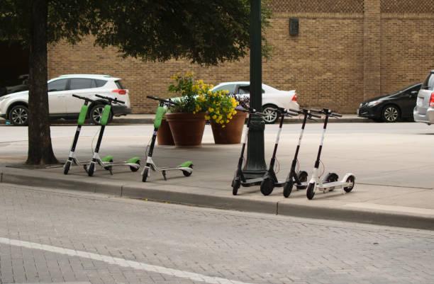 dockless electric scooters on the sidewalk - moto imagens e fotografias de stock