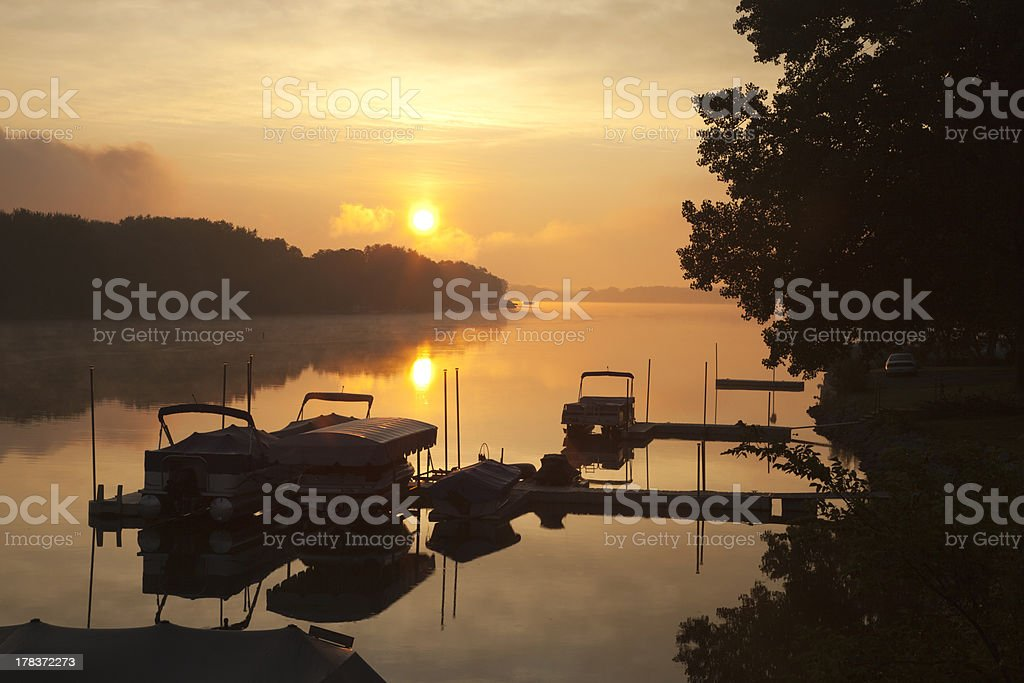 Docks and boats on Wisconsin lake at sunrise stock photo