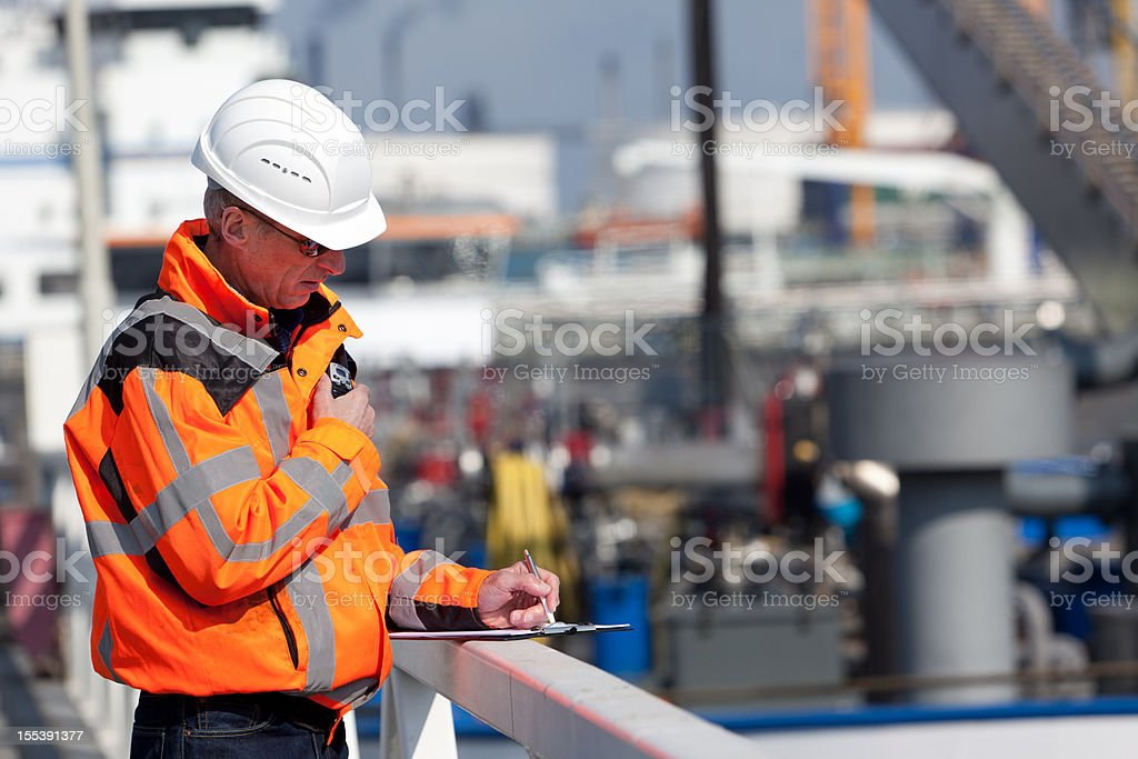 Dockworker giving instructions stock photo