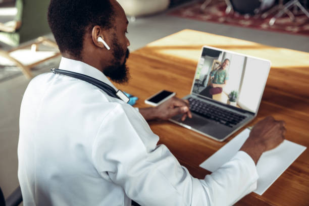 Doctor advising the patient online with laptop. African-american doctor during his videocall, work with patients, explaining recipes for drug. stock photo