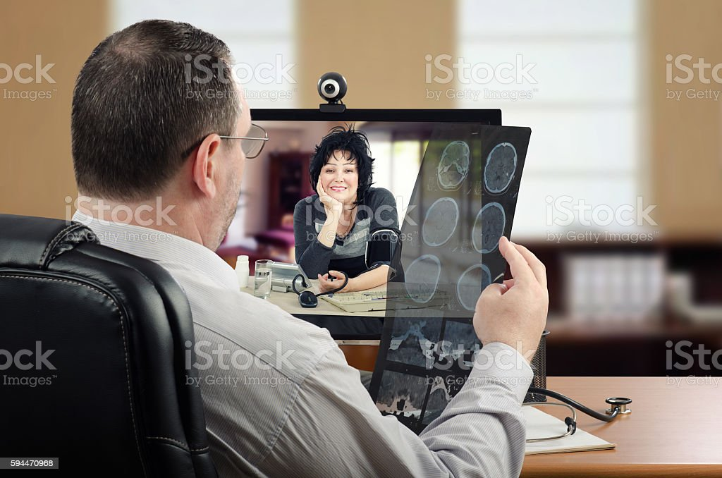 Doctor analyzes brain x-ray results of patient online stock photo