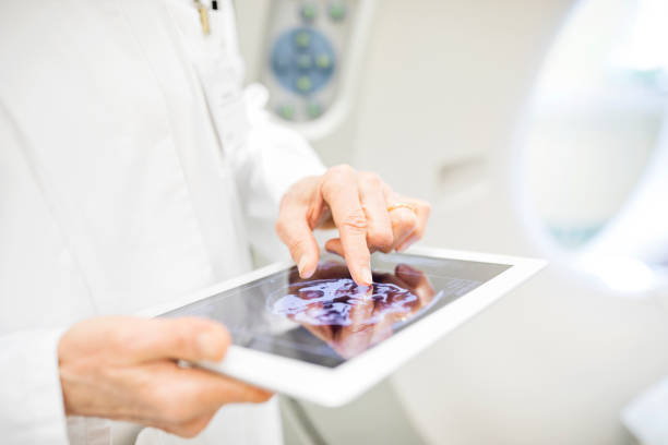 Doctor analyzing X-ray image in digital tablet stock photo