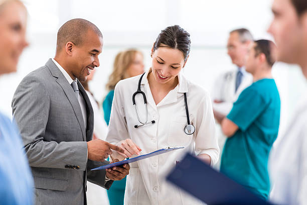 Doctor and African American businessman reading documents together. Young  smiling female doctor cooperating with African American businessman. They are standing together and looking at reports. Other doctors are around them. administrator stock pictures, royalty-free photos & images