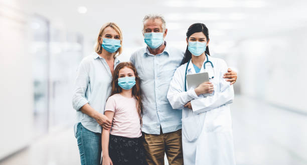 Doctor and family wear face mask in hospital protect from COVID-19. stock photo