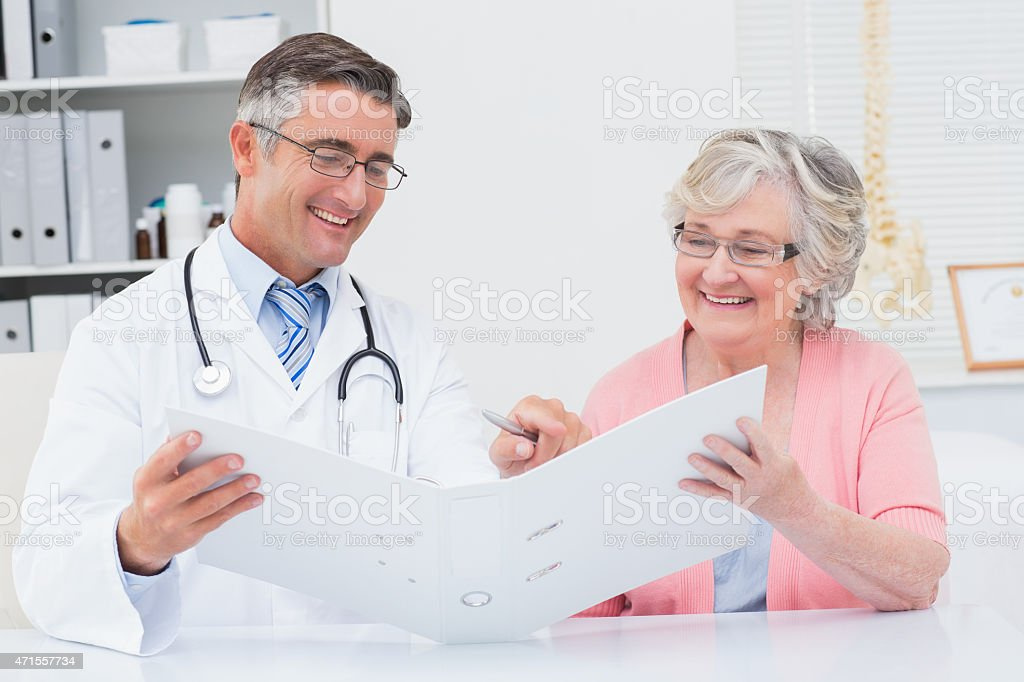 Doctor and female patient looking at reports in file stock photo